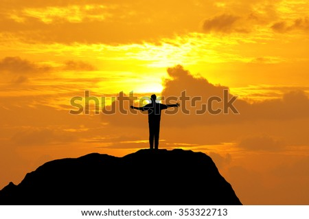 Silhouette of a man open hands on top of mountain during sunset.