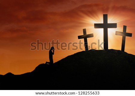 Silhouette of a man praying at the Cross on sunset background