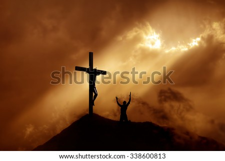Silhouette of a man praying before a cross at sunset concept of religion