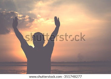 Silhouette of a man raise their hands with enjoy the sunset
