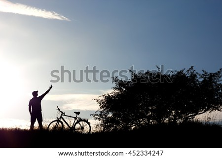 Silhouette of a man raising hand and bicycle on blue sky