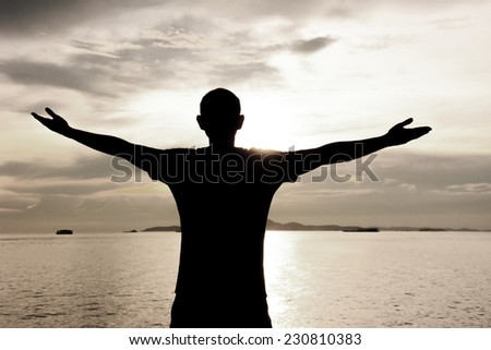 Silhouette of a man raising his arms on sea water & sky background - happy, relax & success concept