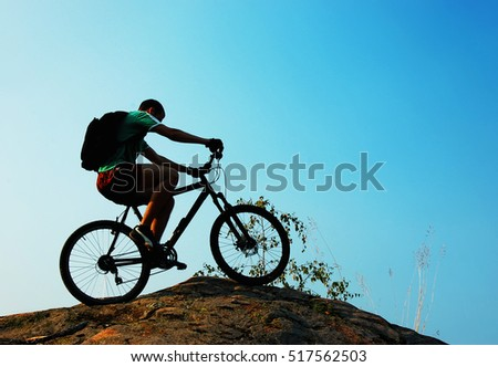 Silhouette of a man riding bike over a mountain rock