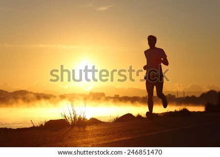 Silhouette of a man running at sunrise with the sun in the background - stock photo