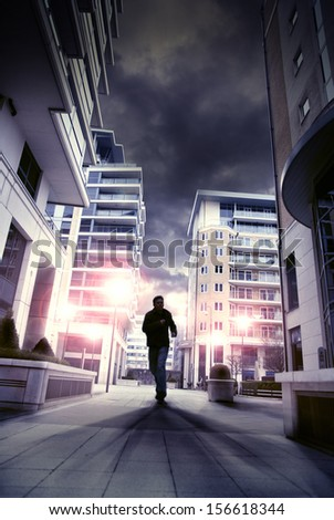 Silhouette of a man running through a city street at night. Flared street lights and strong shadows / silhouette of man running through city - stock photo