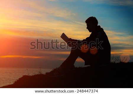 Silhouette of a man sitting on breakwater in evening near sea, reads book  - stock photo