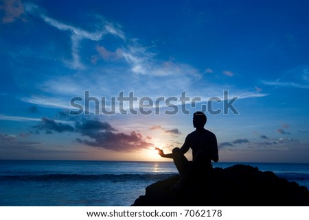 Silhouette of a man sitting on the rock, meditating (and keeping the sun) - stock photo