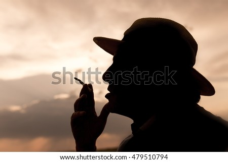 silhouette of a man smoking a cigarette on the sunset background