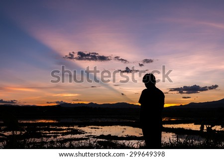 Silhouette of a man standing in a cornfield at sunset reflected in water.