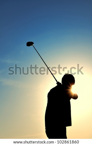 Silhouette of a Man Swinging a Driver - stock photo