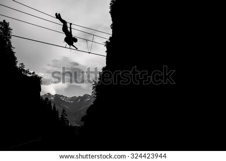 Silhouette of a man traversing rope bridge - stock photo