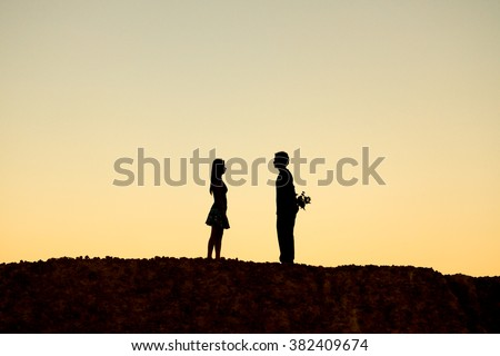 Silhouette of a man trying to surprise a woman by giving a bunch of flowers - stock photo
