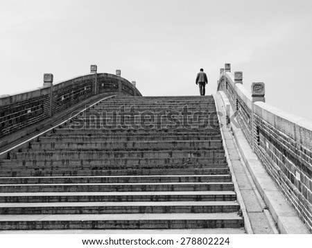 Silhouette of a man walking across an ancient Chinese imperial stonemason bridge, processed in monochrome. - stock photo