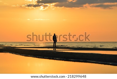 silhouette of a man watching  sunset on a seashore - stock photo