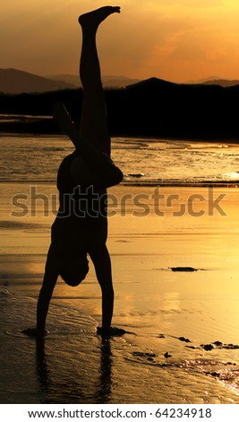 Silhouette of a man who makes a handstand on the beach at sunset - stock photo