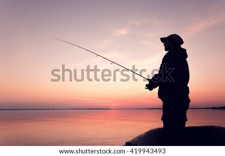 Silhouette of a man with a fishing rod in a boat at sunset