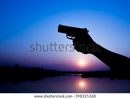 Silhouette of a man with a handgun at sunrise. - stock photo
