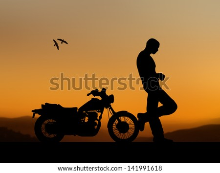 silhouette of a man with a motorcycle on a sunset background - stock photo
