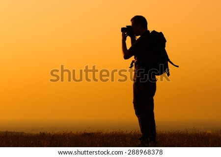 Silhouette of a man with backpack photographing.Hiker photographing - stock photo