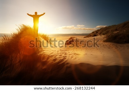Silhouette of a man with hands raised in the sunset on a beach concept for religion, worship, prayer and praise - stock photo