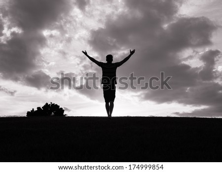 Silhouette of a man with hands raised in the sunset. Religion concept. - stock photo