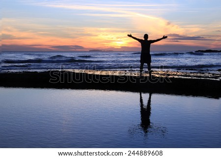 Silhouette of a man with outstretched arms at sunset on a beach.  - stock photo