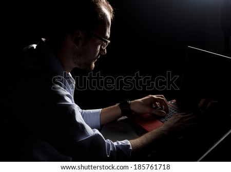 Silhouette of a man working on laptop  - stock photo