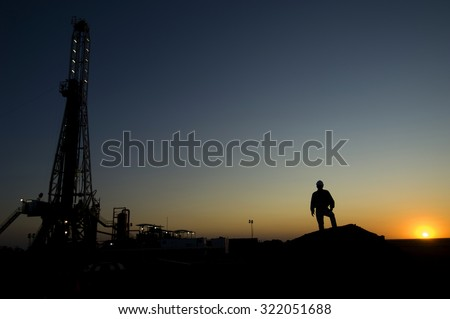 Silhouette of a mining work with a drilling rig in the background - stock photo