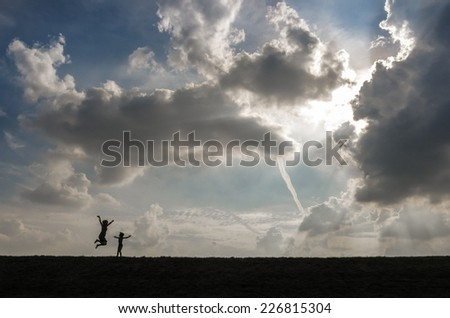 Silhouette of a mother and child jumping up and down in front of a dramatic sky - stock photo