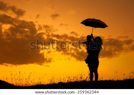 silhouette of a mother and son holding umbrella and playing outdoors at sunset - stock photo