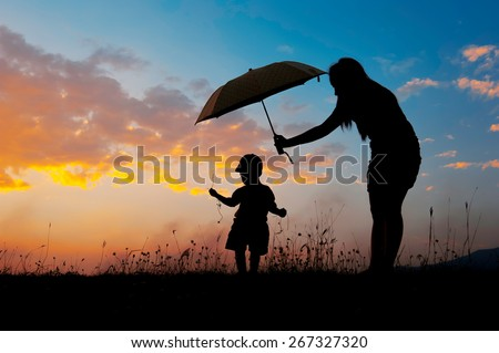 Silhouette of a mother and son holding umbrella and playing outdoors at sunset silhouette - stock photo