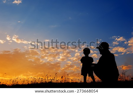 Silhouette of a mother and son playing outdoors at sunset silhouette - stock photo