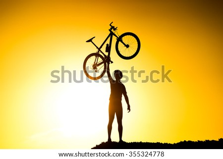 silhouette of a mountain bike cyclist standing on the mountain raising his bike
