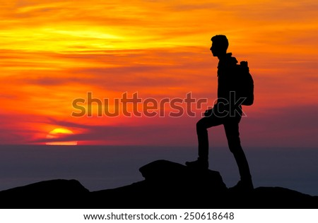 Silhouette of a mountaineer standing on the top at sunset  - stock photo