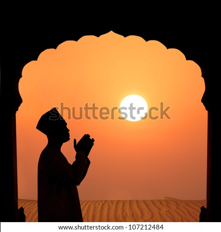 silhouette of a muslim male praying on the desert, islamic architecture - stock photo