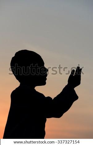 Silhouette of a Muslim praying  - stock photo