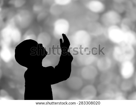 Silhouette of a Muslim praying bokeh  background  - stock photo