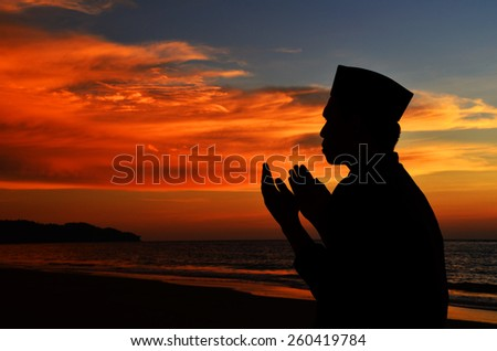 Silhouette of a Muslim praying during sunset. Image has grain or blurry or noise and soft focus when view at full resolution.  (Shallow DOF, slight motion blur)  - stock photo