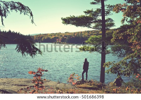Silhouette of a nature photographer standing on a cliff in the sunset light admiring  the North South lake in the Catskill mountains. Vintage processed. Travel, adventure, outdoors and fashion concept