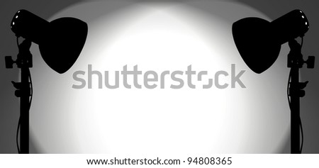 Silhouette of a pair of studio spotlight lighting up a blank white wall with copy space for text. - stock photo