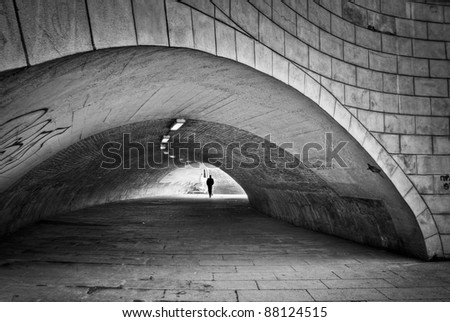silhouette of a person in a tunnel - stock photo