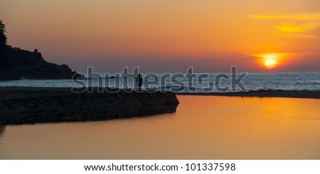 Silhouette of a person walking on jetty at sunset, Sayulita, Nayarit, Mexico - stock photo