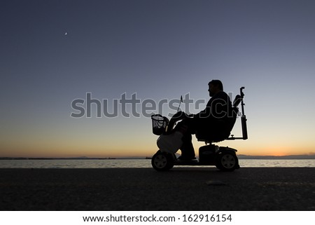 silhouette of a person with disabilities on wheelchair on the sunset - stock photo