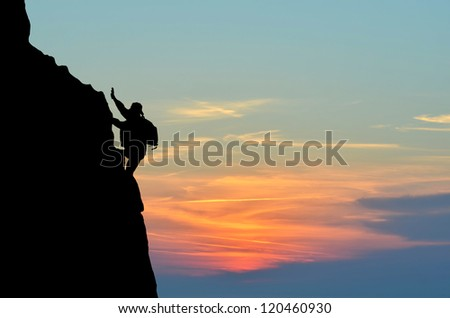 silhouette of a person without insurance climbs the rock in the background of the sunset - stock photo