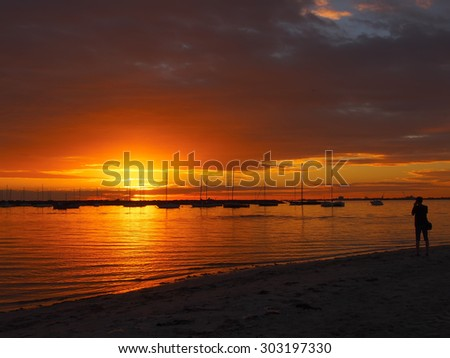 silhouette of a photographer at sunset. St Kilda beach, Melbourne, Australia - stock photo