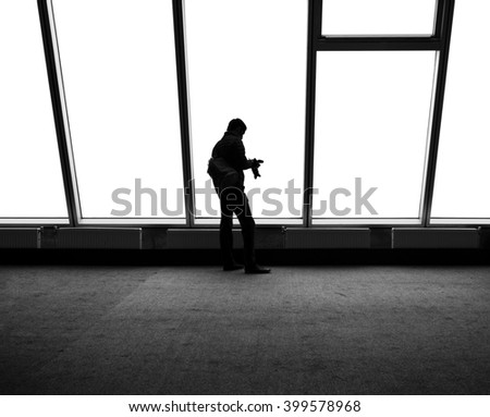 Silhouette of a photographer on the background of a large white window - stock photo