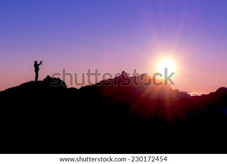 silhouette of a photographer shooting sun rising above the mountains