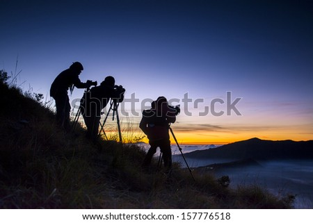 Silhouette of a photographer standing on mountain near by Bromo Valcano, Indonesia