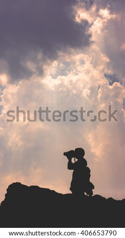 Silhouette of a photographer taking a picture from the top of the cliff