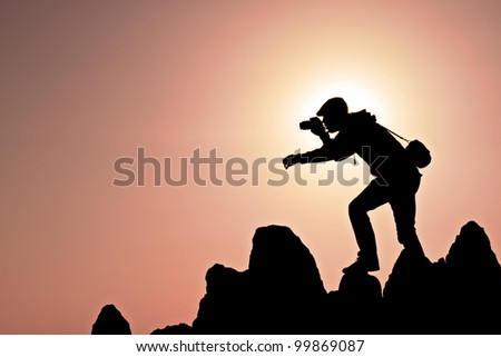 silhouette of a photographer who shoots a sunset on a hill